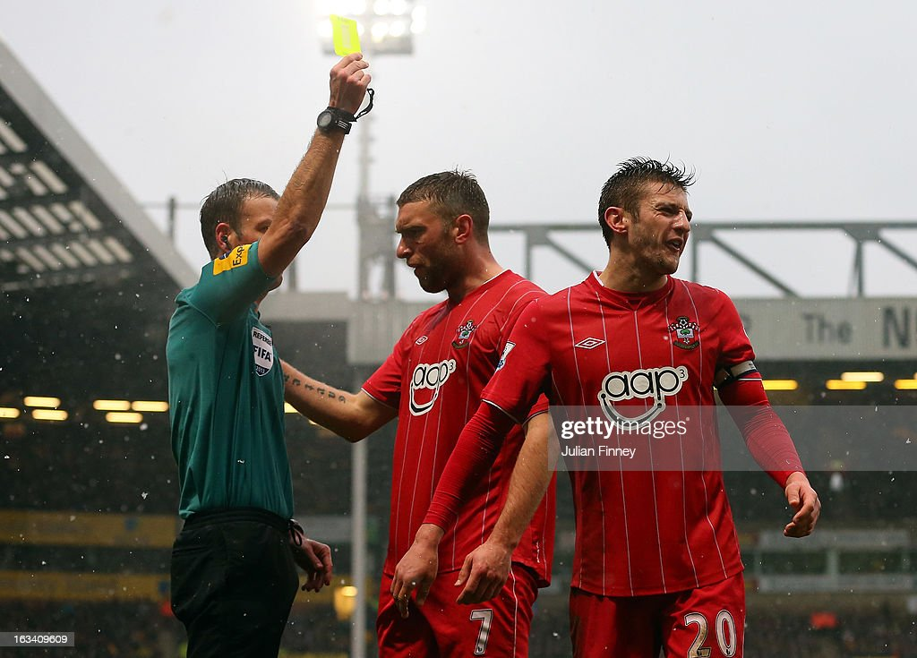 Referee, <a gi-track='captionPersonalityLinkClicked' href=/galleries/search?phrase=Mark+Clattenburg&family=editorial&specificpeople=2108870 ng-click='$event.stopPropagation()'>Mark Clattenburg</a> shows a yellow card to <a gi-track='captionPersonalityLinkClicked' href=/galleries/search?phrase=Adam+Lallana&family=editorial&specificpeople=5475862 ng-click='$event.stopPropagation()'>Adam Lallana</a> of Southampton during the Barclays Premier League match between Norwich City and Southampton at Carrow Road on March 9, 2013 in Norwich, England.