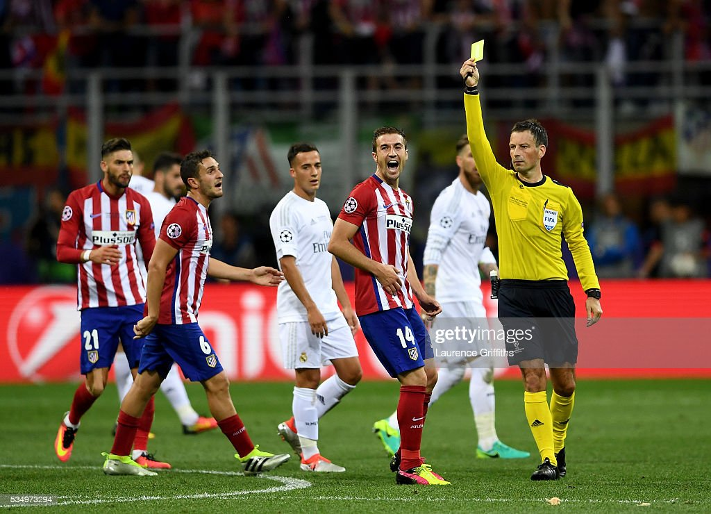 Referee <a gi-track='captionPersonalityLinkClicked' href=/galleries/search?phrase=Mark+Clattenburg&family=editorial&specificpeople=2108870 ng-click='$event.stopPropagation()'>Mark Clattenburg</a> shows a yellow card to <a gi-track='captionPersonalityLinkClicked' href=/galleries/search?phrase=Gabi+-+Soccer+Player&family=editorial&specificpeople=6912055 ng-click='$event.stopPropagation()'>Gabi</a> of Atletico Madrid as he complains about a decision during the UEFA Champions League Final match between Real Madrid and Club Atletico de Madrid at Stadio Giuseppe Meazza on May 28, 2016 in Milan, Italy.