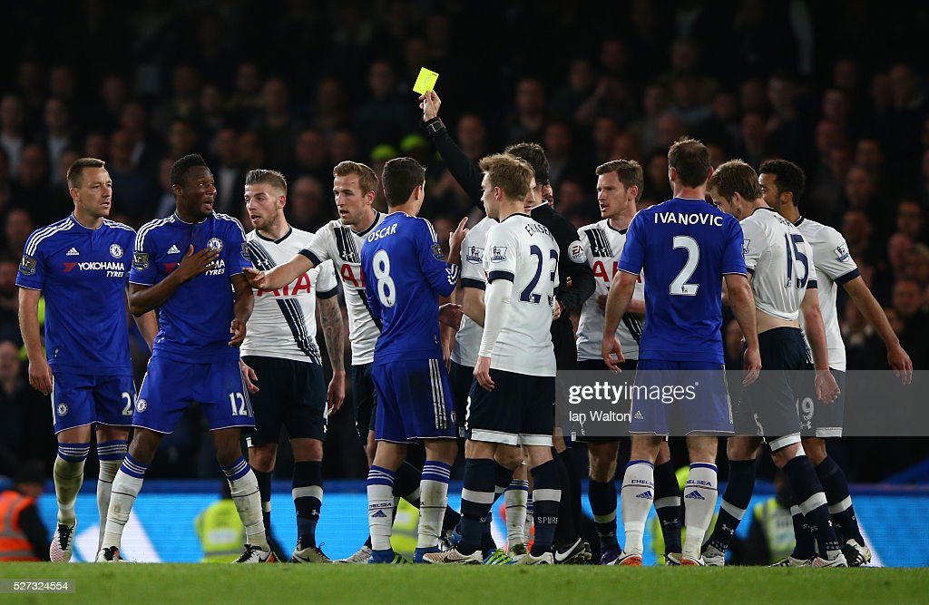 Referee Mark Clattenburg shows a yellow card to John Mikel Obi of Chelsea during the Barclays Premier League match between Chelsea and Tottenham Hotspur at Stamford Bridge on May 02, 2016 in London, England.jd