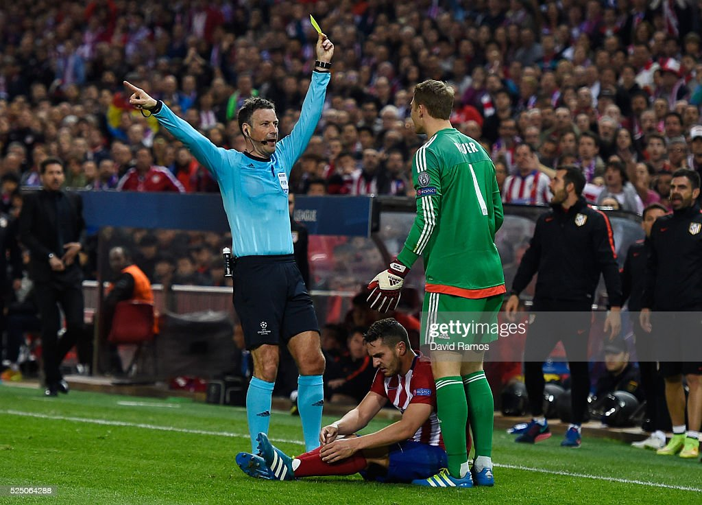 Referee Mark Clattenburg shows a yellow card to Manuel Neuer of Bayern Munich (1) during the UEFA Champions League semi final first leg match between Club Atletico de Madrid and FC Bayern Muenchen at Vincente Calderon on April 27, 2016 in Madrid, Spain.