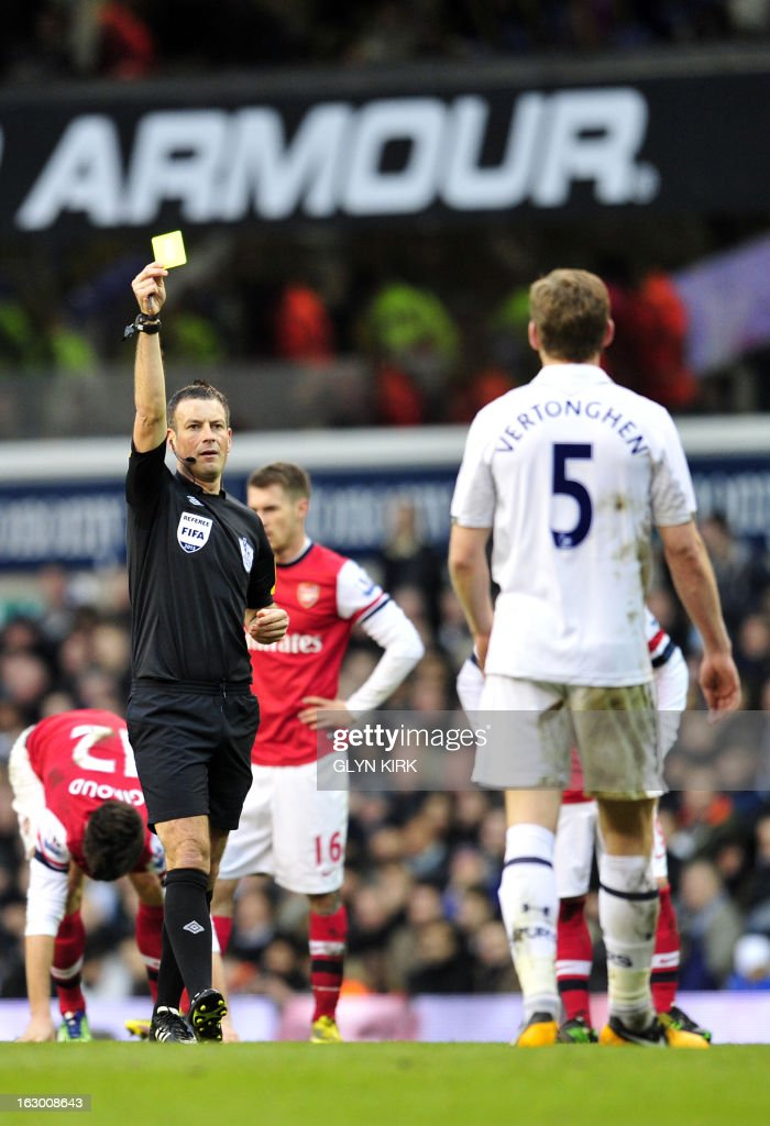 """Referee Mark Clattenburg (L) shows a yellow card to Tottenham Hotspur's Belgian defender Jan Vertonghen (R) during the English Premier League football match between Tottenham Hotspur and Arsenal at White Hart Lane in north London on March 3, 2013. USE. No use with unauthorized audio, video, data, fixture lists, club/league logos or """"live"""" services. Online in-match use limited to 45 images, no video emulation. No use in betting, games or single club/league/player publications"""