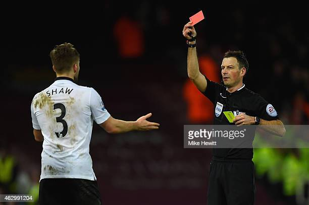 Referee Mark Clattenburg shows Luke Shaw of Manchester United a red card during the Barclays Premier League match between West Ham United and...