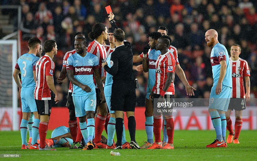 Referee Mark Clattenburg (C) shows Southampton's Kenyan midfielder Victor Wanyama (3L) the red card for a challenge on West Ham United's French midfielder Dimitri Payet (laying on pitch) during the English Premier League football match between Southampton and West Ham United at St Mary's Stadium in Southampton, southern England on February 6, 2016. / AFP / GLYN KIRK / RESTRICTED TO EDITORIAL USE. No use with unauthorized audio, video, data, fixture lists, club/league logos or 'live' services. Online in-match use limited to 75 images, no video emulation. No use in betting, games or single club/league/player publications. /