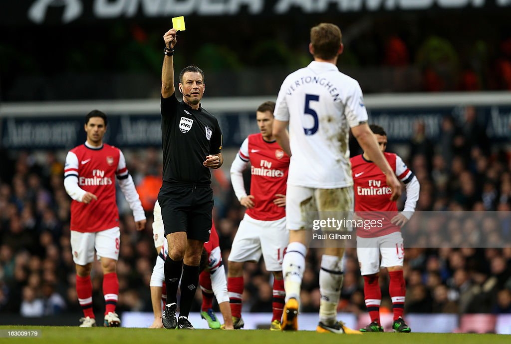 Referee Mark Clattenburg shows the yellow card to Jan Vertonghen of Spurs during the Barclays Premier League match between Tottenham Hotspur and Arsenal FC at White Hart Lane on March 3, 2013 in London, England.