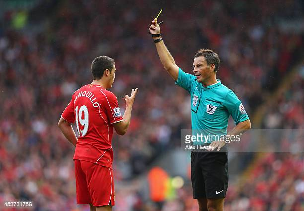 Referee Mark Clattenburg shows the yellow card to Javi Manquillo of Liverpool during the Barclays Premier League match between Liverpool and...