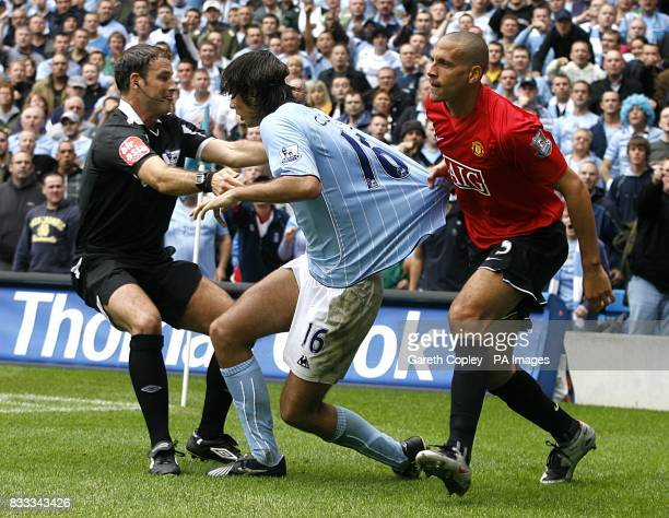 Referee Mark Clattenburg steps in to stop an altercation between Manchester City's Vedran Corluka and Manchester United's Rio Ferdinand