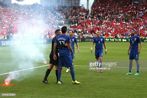 Referee Mark Clattenburg ushers Mario Mandzukic of Croatia away from a flare that was thrown on the pitch during the UEFA Euro 2016 Group D match...