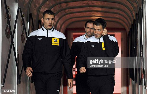 Referee Mark Clattenburg walks out onto the pitch with his two assistants as they warm up during the Barclays Premier League match between...