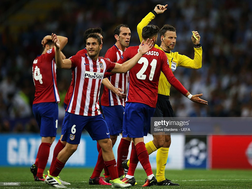 Referee Mark Clattenburg (1st R) walks toward Sergio Ramos of Real Madrid before showing an yellow card after fouling Yannick Carrasco (2nd R) of Atletico Madrid during the UEFA Champions League Final between Real Madrid and Club Atletico de Madrid at Stadio Giuseppe Meazza on May 28, 2016 in Milan, Italy..