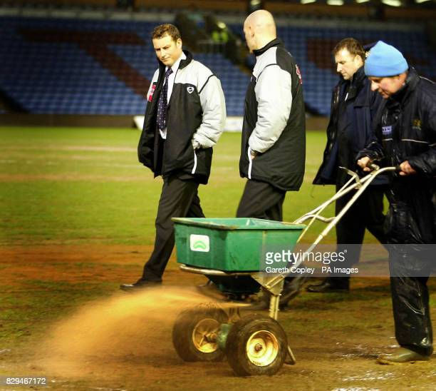 Referee Mark Clattenburg watches groundstaff as they try to dry out the pitch at Turf Moor