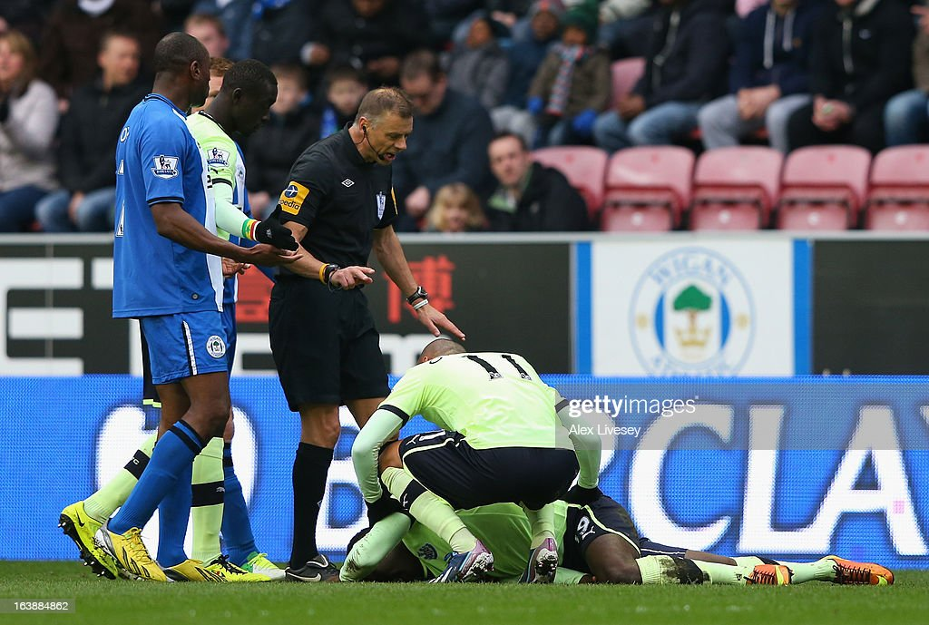 Referee Mark Halsey checks on Massadio Haidara of Newcastle United following a challenge by Callum McManaman of Wigan Athletic during the Barclays Premier League match between Wigan Athletic and Newcastle United at the DW Stadium on March 17, 2013 in Wigan, England.