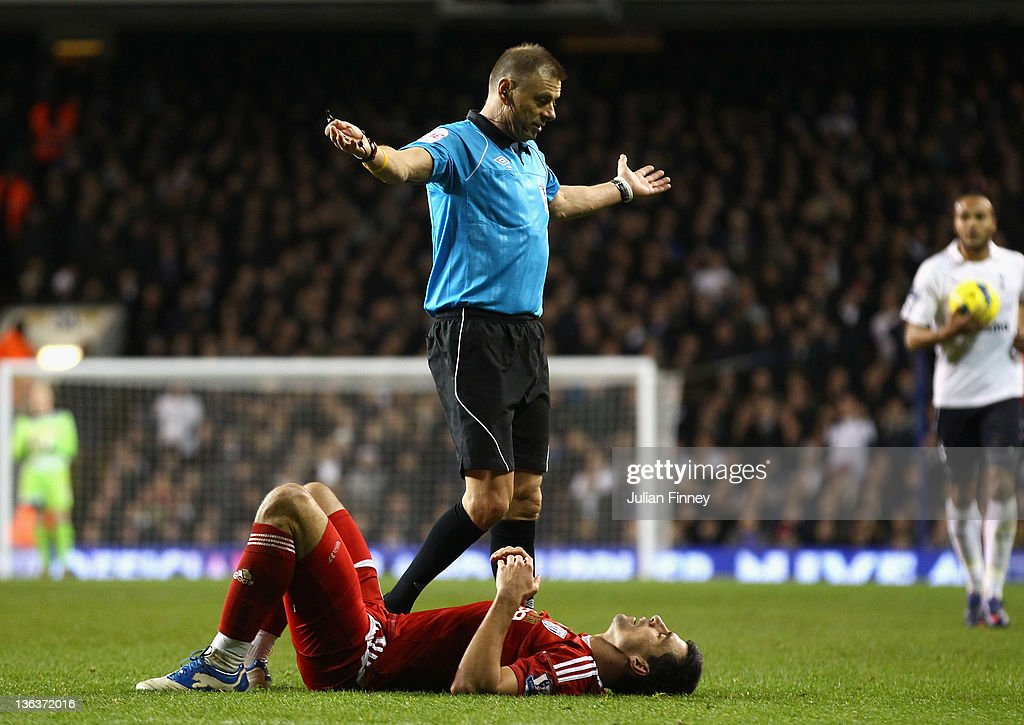 Referee <a gi-track='captionPersonalityLinkClicked' href=/galleries/search?phrase=Mark+Halsey&family=editorial&specificpeople=224397 ng-click='$event.stopPropagation()'>Mark Halsey</a> reacts as <a gi-track='captionPersonalityLinkClicked' href=/galleries/search?phrase=Paul+Scharner&family=editorial&specificpeople=620484 ng-click='$event.stopPropagation()'>Paul Scharner</a> of West Bromwich Albion lies on the pitch during the Barclays Premier League match between Tottenham Hotspur and West Bromwich Albion at White Hart Lane on January 3, 2012 in London, England.