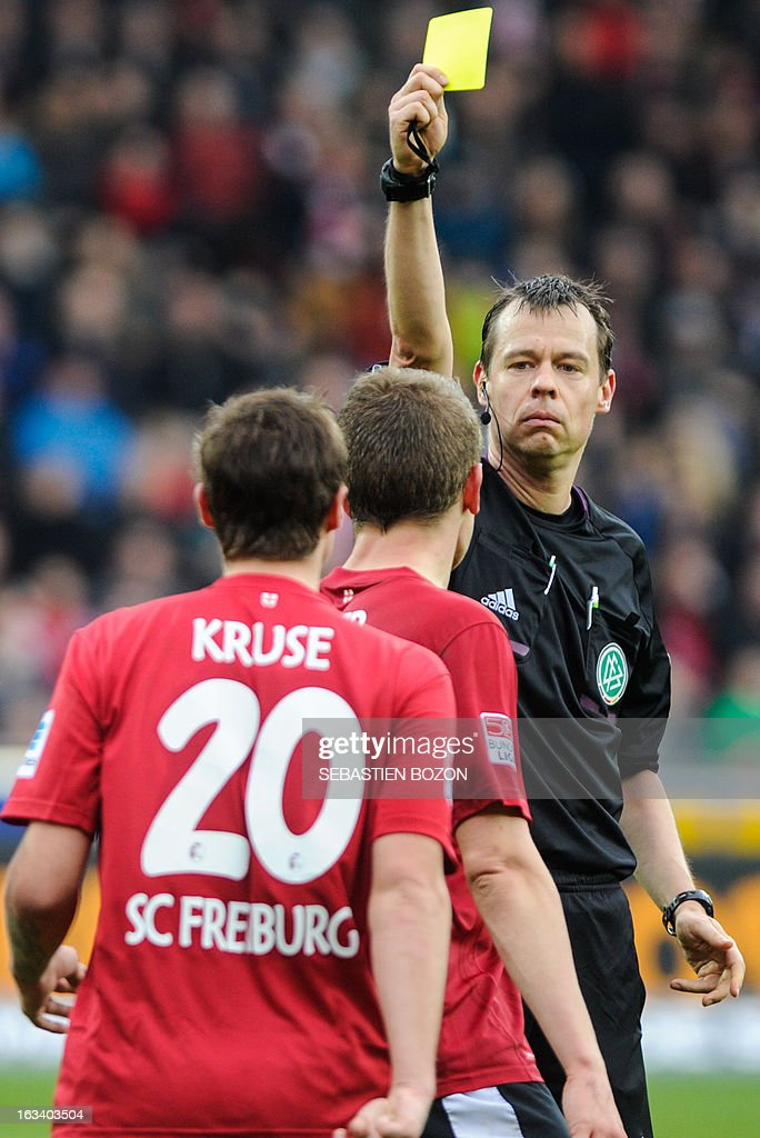 Referee Markus Schmidt (R) shows Freiburg's midfielder Max Kruse (L) the yellow card during the German first division Bundesliga football match SC Freiburg vs Wolfsburg in Freiburg, southern Germany, on March 9, 2013. AFP PHOTO / SEBASTIEN BOZON
