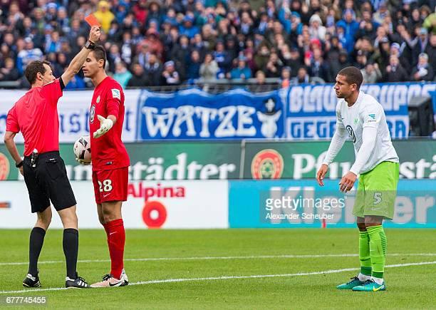 Referee Markus Schmidt shows Jeffrey Bruma of VfL Wolfsburg the red card during the Bundesliga match between SV Darmstadt 98 and VfL Wolfsburg at...
