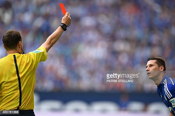 Referee Markus Schmidt shows the red card to Schalke's midfielder Julian Draxler during the German first division Bundesliga football match FC...