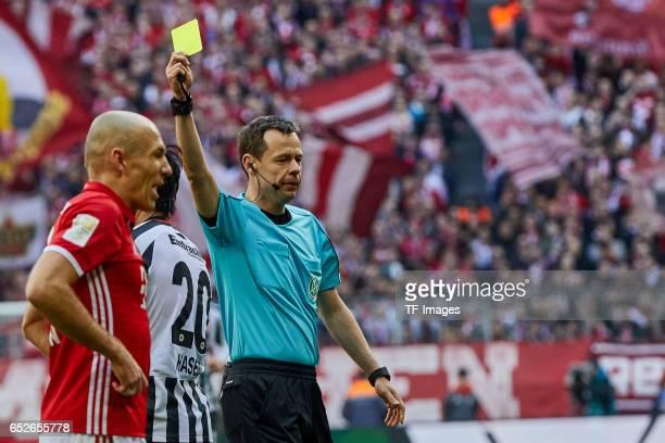 Referee Markus Schmidt zeigt Makoto Hasebe of Frankfurt vr die gelbe Karte gestures during the Bundesliga match between Bayern Muenchen and Eintracht...