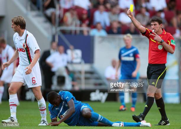 Referee Markus Wingenbach shows the yellow card to Jonas de Roeck of Augsburg after fouling Edson Braafheid of Hoffenheim during the Bundesliga match...
