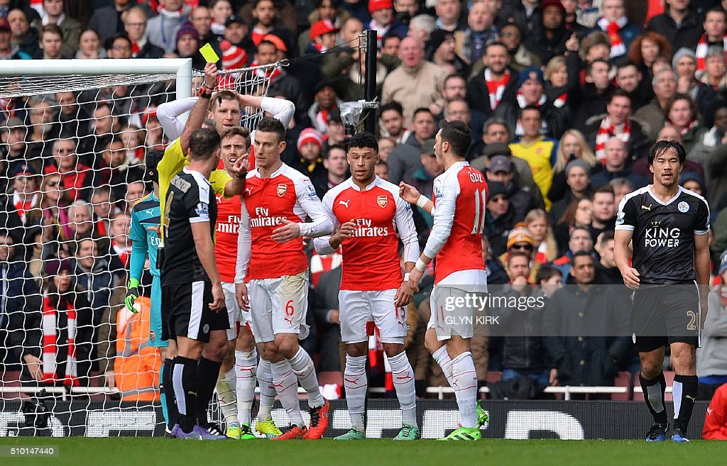 Referee Martin Atkiinson (L) shows a yellow card to Arsenal's French defender Laurent Koscielny (5L) and at the same time awards Leicester a penalty for a challenge by Arsenal's Spanish defender Nacho Monreal (4L) on Leicester City's English striker Jamie Vardy (not pictured) during the English Premier League football match between Arsenal and Leicester at the Emirates Stadium in London on February 14, 2016. / AFP / GLYN KIRK / RESTRICTED TO EDITORIAL USE. No use with unauthorized audio, video, data, fixture lists, club/league logos or 'live' services. Online in-match use limited to 75 images, no video emulation. No use in betting, games or single club/league/player publications. /