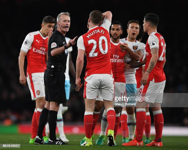 Referee Martin Atkinson and Shkodran Mustafi of Arsenal exchange words during the Premier League match between Arsenal and West Ham United at the...