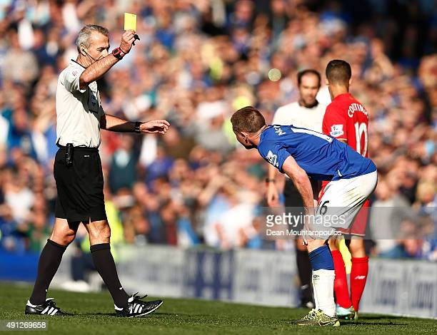 Referee Martin Atkinson books James McCarthy of Everton during the Barclays Premier League match between Everton and Liverpool at Goodison Park on...