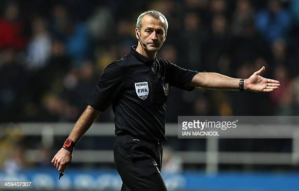 Referee Martin Atkinson gestures during the English Premier League football match between Newcastle United and Stoke City at at St James' Park in...