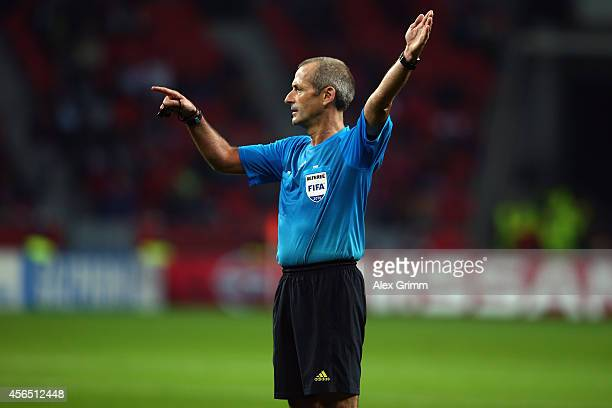 Referee Martin Atkinson gestures during the UEFA Champions League Group C match between Bayer 04 Leverkusen and SL Benfica at BayArena on October 1...