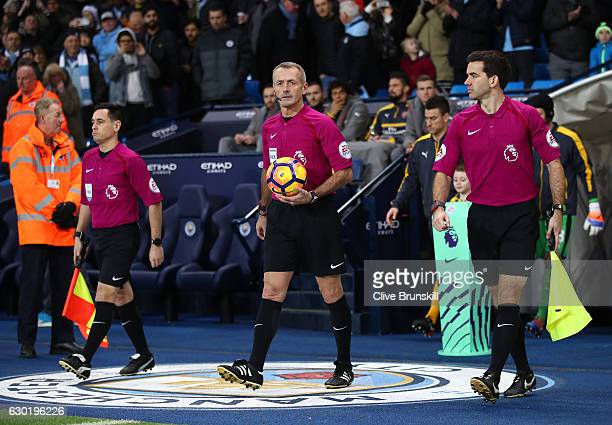 Referee Martin Atkinson leads out the teams prior to kick off during the Premier League match between Manchester City and Arsenal at the Etihad...