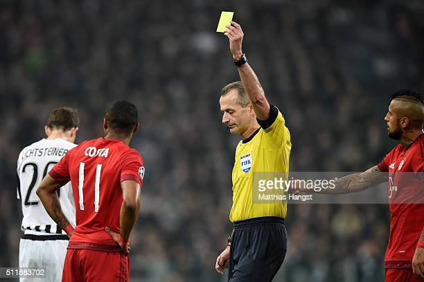 Referee Martin Atkinson of England shows the yellow card to Douglas Costa of Bayern Muenchen during the UEFA Champions League round of 16 first leg...