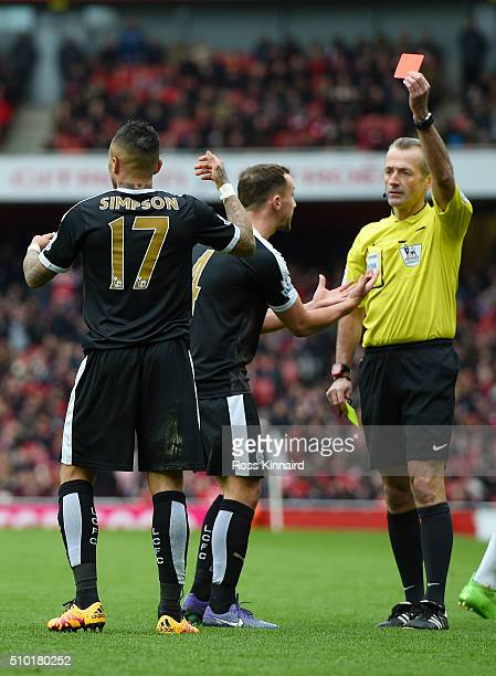 Referee Martin Atkinson shows a red card to Danny Simpson of Leicester City during the Barclays Premier League match between Arsenal and Leicester...