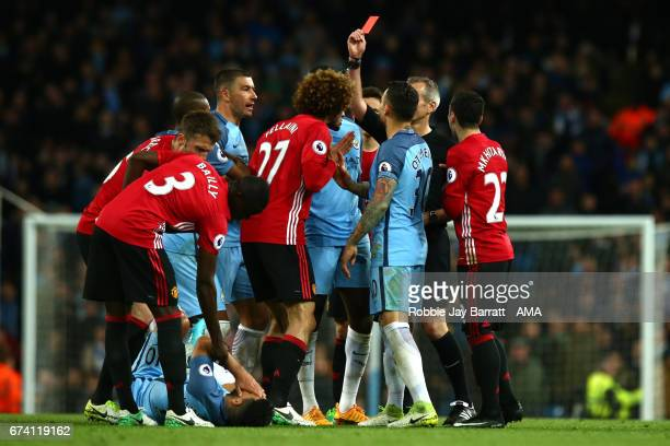 Referee Martin Atkinson shows a red card to Marouane Fellaini of Manchester United during the Premier League match between Manchester City and...