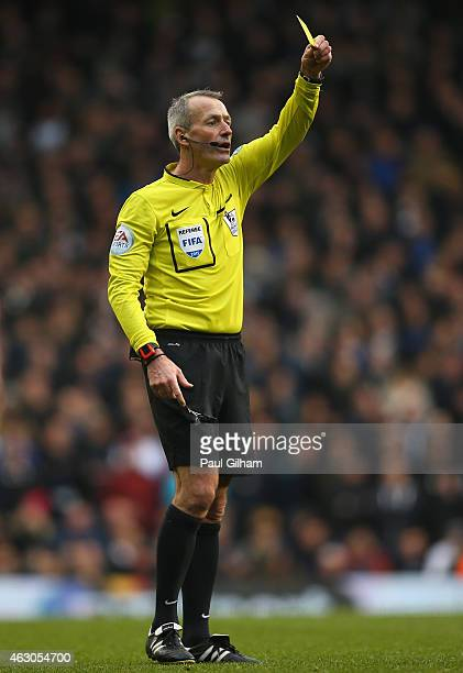 Referee Martin Atkinson shows a yellow card during the Barclays Premier League match between Tottenham Hotspur and Arsenal at White Hart Lane on...