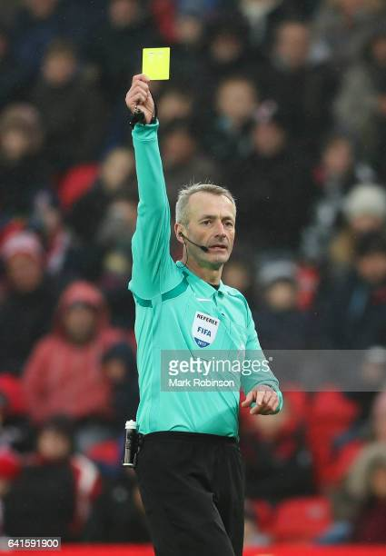 Referee Martin Atkinson shows a yellow card during the Premier League match between Stoke City and Crystal Palace at Bet365 Stadium on February 11...