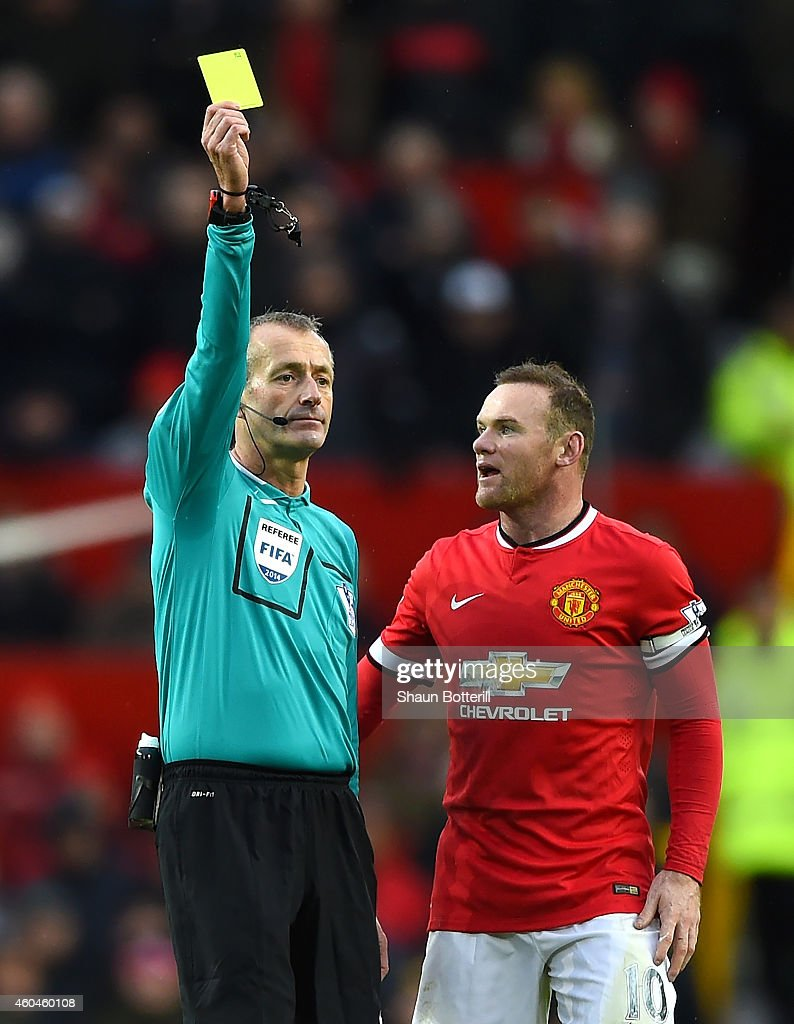 Referee Martin Atkinson shows a yellow card to Wayne Rooney of Manchester United during the Barclays Premier League match between Manchester United...