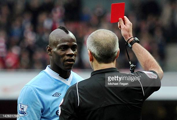 Referee Martin Atkinson shows Mario Balotelli of Man City a red card during the Barclays Premier League match between Arsenal and Manchester City at...