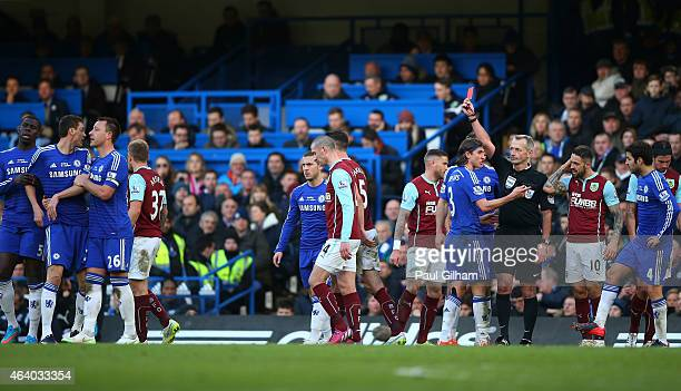 Referee Martin Atkinson shows the red card to Nemanja Matic of Chelsea during the Barclays Premier League match between Chelsea and Burnley at...