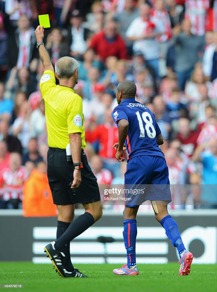 Referee Martin Atkinson shows the yellow card to Ashley Young of Manchester United for diving during the Barclays Premier League match between...