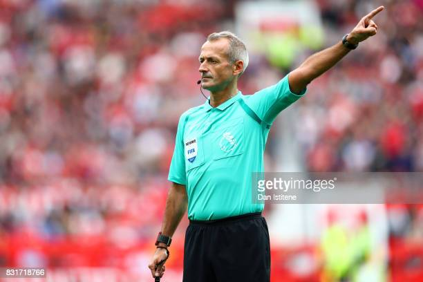 Referee Martin Atkinson signals during the Premier League match between Manchester United and West Ham United at Old Trafford on August 13 2017 in...