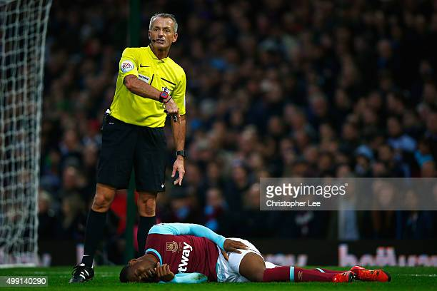Referee Martin Atkinson stands over an injured Diafra Sakho of West Ham United during the Barclays Premier League match between West Ham United and...