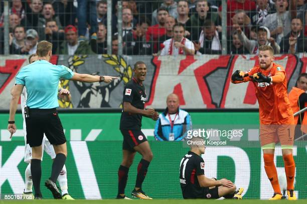 Referee Martin Petersen points to the penalty spot after goalkeeper Timo Horn of Koeln fouled Mijat Gacinovic of Frankfurt during the Bundesliga...