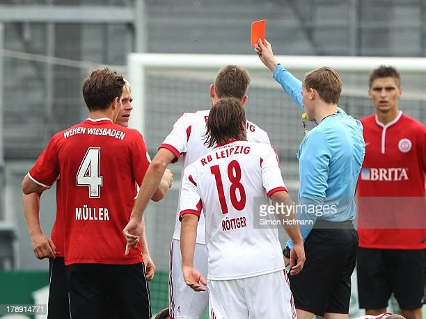 Referee Martin Petersen shows the red card to Michael Wiemann of Wiesbaden during the Third Bundesliga match between SV Wehen Wiesbaden and...