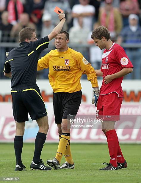Referee Martin Thomsen presents the red card to Florian Hoernig of Regensburg during the Third League match between SSV Jahn Regensburg v Eintracht...