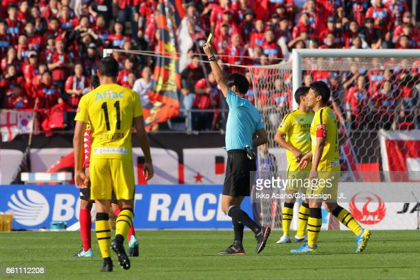 Referee Masaaki Iemoto shows a yellow card to Cristiano of Kashiwa Reysol during the JLeague J1 match between Consadole Sapporo and Kashiwa Reysol at...