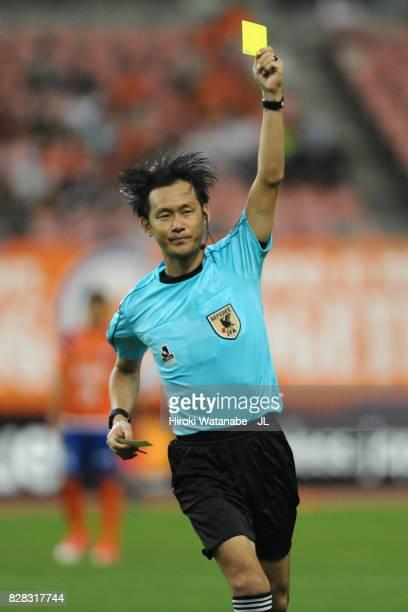 Referee Masaaki Iemoto shows a yellow card to Douglas Tanque of Albirex Niigata during the JLeague J1 match between Albirex Niigata and Kawasaki...