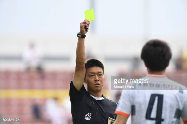 Referee Masaki Tsuruoka shows the yellow card to Takashi Uchino of AC Nagano Parceiro during the JLeague J3 match between Giravanz Kitakyushu and AC...