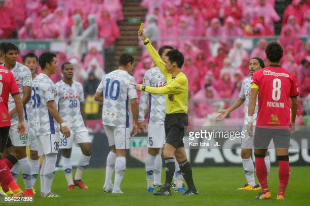 Referee Masuya Ueda shows a yellow card to Eder Lima of Ventforet Kofu after fouling Matej Jonjic of Cerezo Osaka during the JLeague J1 match between...