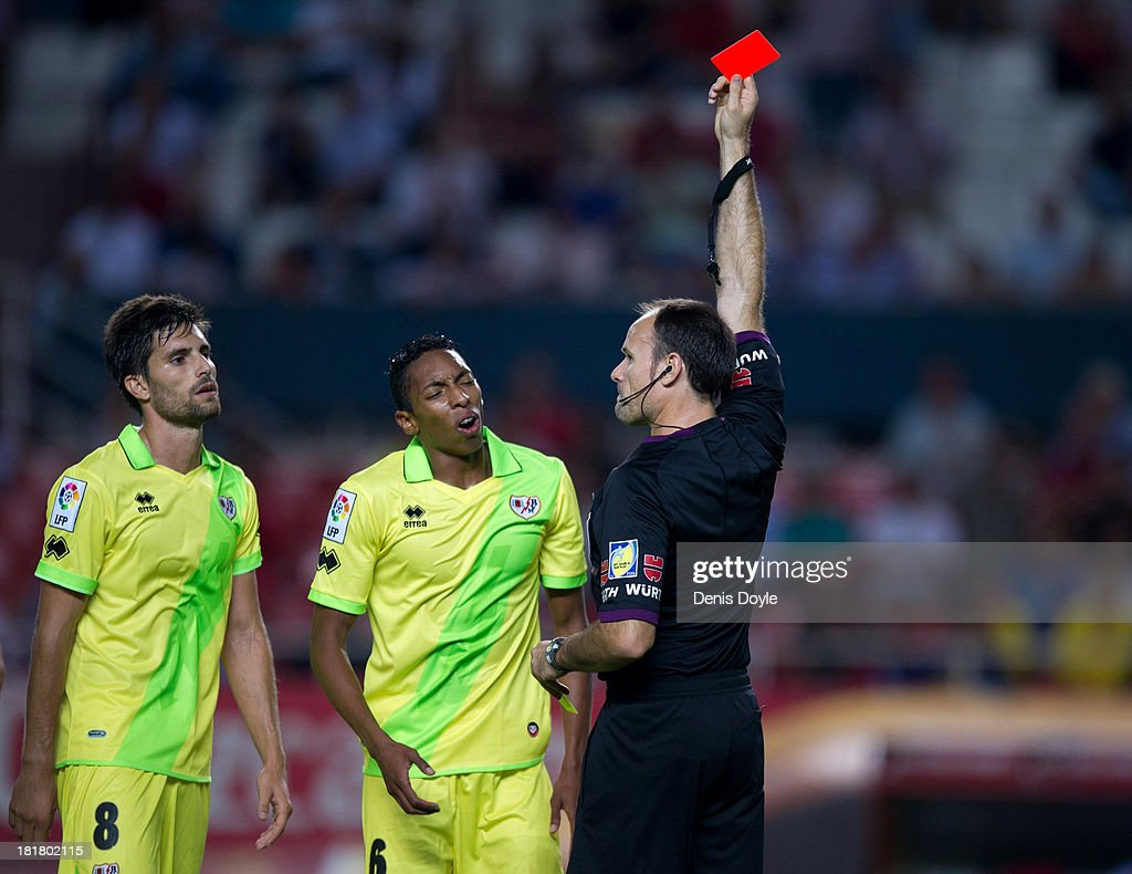 Referee Mateu Lahoz shows Alejandro Galvez (unseen) of Rayo Vallecano the red card while teammates Adrian Gonzalez (L) and Johan Mojica look on during the La liga match between Sevilla FC and Rayo Vallecano de Madrid at Estadio Ramon Sanchez Pizjuan on September 25, 2013 in Seville, Spain.