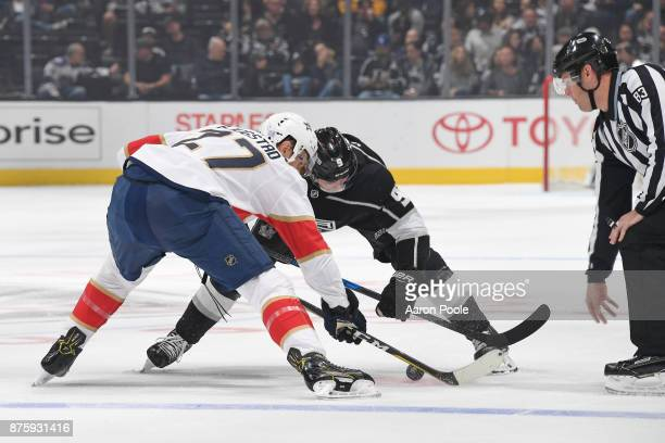 Referee Matt MacPherson initiates the faceoff between Adrian Kempe of the Los Angeles Kings and Nick Bjugstad of the Florida Panthers during a game...