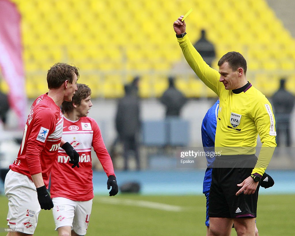 Referee Maxim Layushkin shows a yellow card to <a gi-track='captionPersonalityLinkClicked' href=/galleries/search?phrase=Kim+Kallstrom&family=editorial&specificpeople=539780 ng-click='$event.stopPropagation()'>Kim Kallstrom</a> (L) of FC Spartak Moscow during the Russian Premier League match between FC Spartak Moscow and FC Dynamo Moscow at the Luzhniki Stadium on November 25, 2012 in Moscow, Russia.