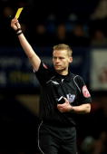 Referee Michael Jones awards a yellow card during the Barclays Premier League match between Portsmouth and Birmingham City at Fratton Park on March 9...