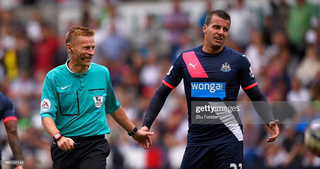 Referee Michael Jones shares a joke with Newcastle player Steven Tyalor (r) during the Barclays Premier League match between Swansea City and Newcastle United at the Liberty stadium on August 15, 2015 in Swansea, United Kingdom.